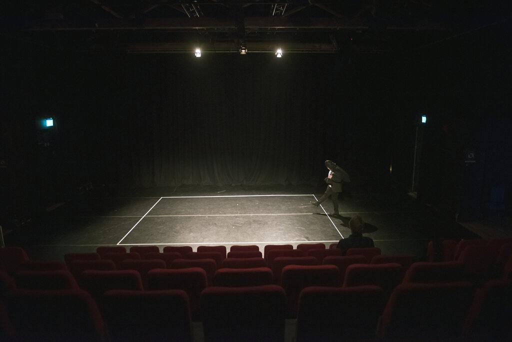 Omgivningen är svart. Bara en scengolvet där en vit fyrkant är upptejpad är upplyst. Från höger i bilden står en svart gestalt och kollar i backen, en benen är lyft, på väg att ta ett steg in i rutan. I förgrunden skymtar tomma röda säten där publiken kommer att sitta.
