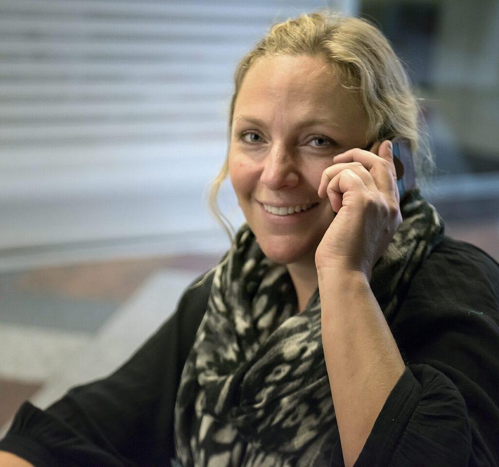 Porträtt av Elin Persson. Elin är en medelålderskvinna med blont uppsatt hår och blåa ögon. Hon tittar in i kameran och ler brett mot oss medan hon håller en telefon mot örat. Elin är klädd i svart med en mönstrad svartvitt scarf om halsen.