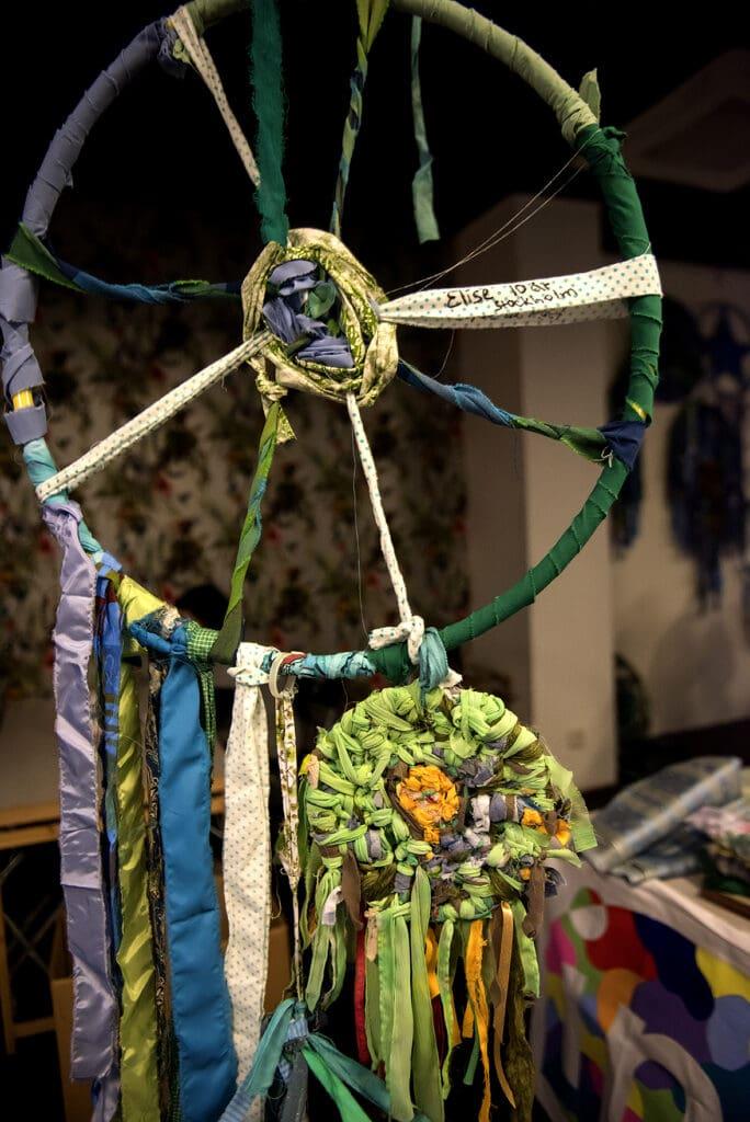 """En stor rockring är lindad och flätad med mönstrade färger i grönt, blått, lila och gult. Tyget är flätat så det påminner om ett cykelhjul, med remsor som möts i mitten. Några tyg-girlanger hänger från den och ringen hänger från taket. En tygremsa har """"Elise 10 år Stockholm"""" skrivet på sig. Nedtill i den stora ringen hänger en liten ring med ett kompakt flätat mönster, mest i grönt med orangea och bruna inslag."""