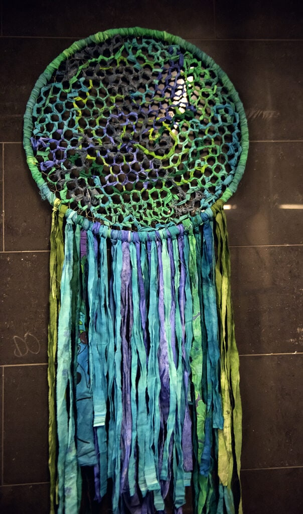 En ring hänger mot en brunaktig vägg. Färgerna går i bjärta blåa, gröna och lila nyanser. Inuti ringen är ett hönsnät vars rutor omsorgsfullt har lindats med tygremsor, en och en. Mönstret påminner om en bivaxkaka. Nertill på ringen hänger en massa tyg-girlanger.