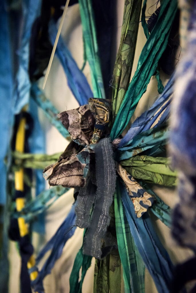 Fokus på det flätade navet i en rockring som är lindad och flätad med mönstrade färger i en explosion av grönt, blått och turkos. Tygremsorna är bundna så det går ihop i mitten, som ekrarna i ett cykelhjul. I navet på ringen verkar någon ha knutit en tygrosett i brunt och blått.