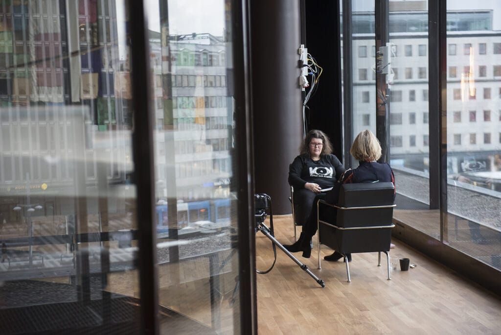 En bit bort i bilden, Hanna sitter i fåtöljen och tittar på Linda. I knäet ligger några papper med frågor som hon ställer till Linda. I förgrunden till vänster i bilden syns delar av en stor glasrundel som speglar Stockholms stadsmiljö från de stora fönsterna till höger i bilden.
