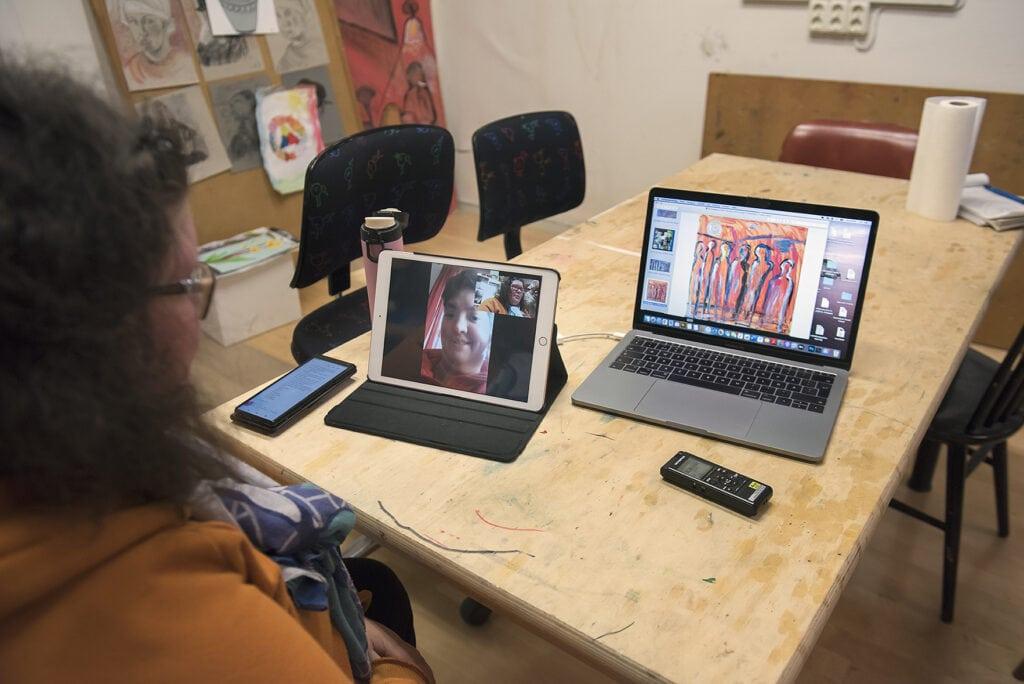 Foto av Hanna som delvis syns i profil i förgrunden och är omgiven av elektronik. På ett bord framför sig har hon en dator med en av Emelies konstverk på. Framför datorn ligger en diktafon. Bredvid datorn står en surfplatta där Emelies ansikte syns. Till vänster om surfplattan ligger en telefon.