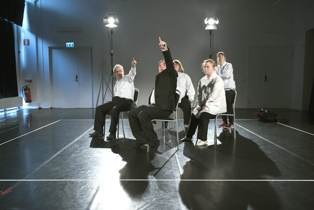 I mitten på den mörka scenen sitter fyra personer på stolar i två rader och bakom dem står en femte person. Runt dem är en vit ruta tejpad i golvet. Alla skådespelare har vita skjortor och svarta byxor, utom Joakim. Joakim är klädd i en svart kostym med vit skjorta, han pekar på något högt upp. Johannes strax bredvid Joakim. Han pekar mot samma sak som Joakim. Bakom dem sitter Josefin och Sofia. Josefin tittar på det Joakim och Johannes pekar på. Sofia tittar på Joakim. Miriam står längst bak med korslagda armar och tittar där Joakim pekar.