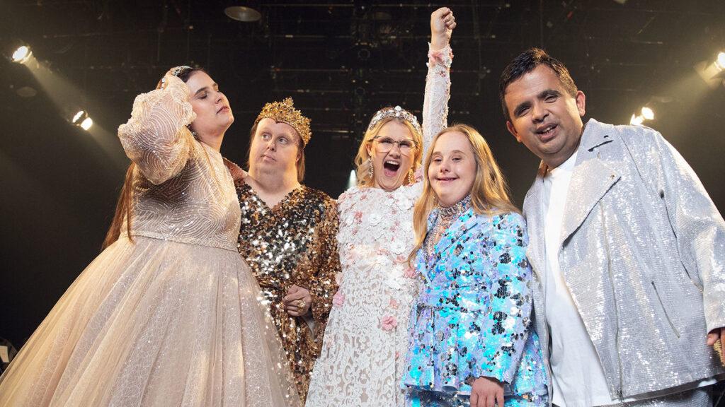 Ett gruppfoto på gänget från Glada Hudik med vitklädd Emma Örtlund i mitten som lyfter en knuten näve och ser ut att skrika ja! Närmast till vänster om henne står Nicklas Hillberg i guldglittrande kläder med en krona på huvudet och kollar på Kitty Jonsson. Kitty är klädd i en beige-vit glittrande klänning. Hon verkar styrka sitt långa bruna hår bakåt örat, samtidigt som hon blundar och vänder huvudet upp mot taket. Till höger om Emma står Ida Jonsson i en ljusblå och silverglittrande kostym, Hon har långt rödblont hår och ler in i kameran. Bredvid Ida står Alexander Rådlund och ler mot kameran. Han har mörkt kortklippt hår och är klädd inte silvrig kostym med en vit tröja under.