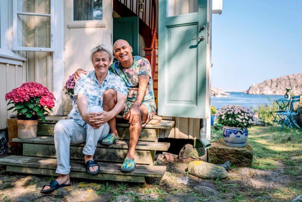 På en trappa framför ingången ett äldre trähus i ljusa pastellfärger, sitter Lars med ena knäet uppdraget, han omfamnar både sitt och Juniors knä. Junior sitter bredvid i med ena armen om Lars. De har ljusa, mönstrade och färgglada kläder på sig. I bakgrunden skymtar havet och Bohusläns klippor.