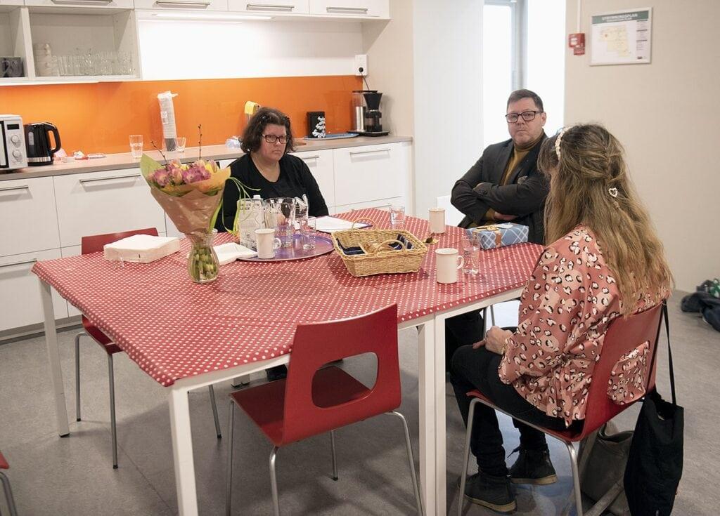 Foto: Hanna i samtal med Per och Tiina. Runt ett rektangulärt bord med en röd duk med vita prickar i en ljus köksmiljö, sitter Hanna, Per och Tiina. Tiina har ryggen mot oss och hennes väska hänger på ryggstödet. Hanna och Per tittar på Tiina. På bordet står en blombukett, kaffekoppar, fikabröd och en bricka med glas och porslin.