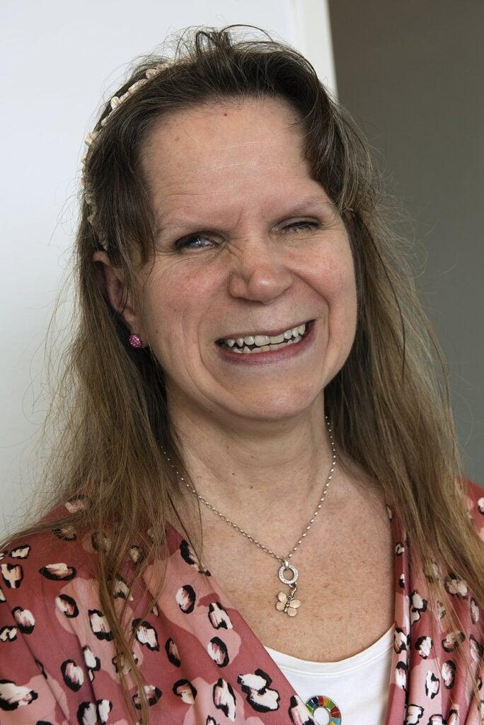 Foto: Porträtt på Tiina Nummi Södergren. Tiina ler brett mot kameran. Hennes vänstra öga är delvis stängt och det högra ögat tycks möta vår blick. Tiina har långt brunt hår och en lugg delad i bena som ramar in hennes ansikte. I håret har hon ett blomsterliknande hårband och i ena örsnibben anas ett rosaglittrande örhänge. Tina har en mörk, mjukrosa blus med några ljusrosa inslag, som liknar stora blomblad. Blusen har ytterligare mönster som liknar små kronblad i vitt med svarta och mörkrosa inslag. Hon har ett halsband med en liten ljusrosa fjäril.